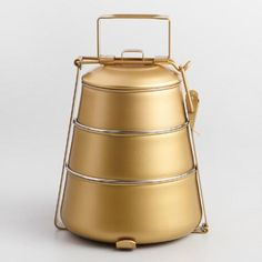 Featuring a sophisticated gold finish, our exclusive tiffin is a tribute to the traditional metal lunch box used widely throughout India and Southern Asia. This chic, tapered version includes three separate tiers, making it perfect for midday meals, picnics or snacking on the go.