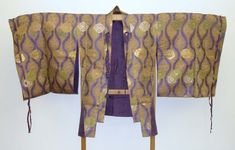 Samurai's two piece hitatare outfit woven in gold, violet, and green silk and unglossed silk threads with roundel of phoenixes and foliage on a design of stylised phoenix tails on a beige ground with tassels. Edo Period. British Museum
