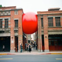 Kurt Perschke's traveling public art installation RedBall has traversed the globe, appearing in many more cities, as well as internationally.     The massive vinyl ball has been wedged in every nook and cranny in its host cities, from in between buildings to underneath bus stops.    ~Apartment Therapy~