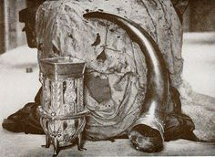 The Dunvegan Cup, Fairy Flag, and Sir Rory Mor's Horn are heirlooms of the MacLeods of Dunvegan. This photo was taken sometime before 1927.  The Fairy Flag (Scottish Gaelic: Am Bratach Sìth) is an heirloom of the chiefs of Clan MacLeod. The Fairy Flag is known for the numerous traditions of fairies, and magical properties associated with it. The flag is made of silk, is yellow or brown in colour, and measures about 18 inches (46cm) squared.