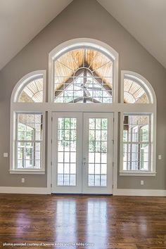 French doors are surrounded by floor-to-ceiling windows in this great room! The McKibbon home design 1119. #WeDesignDreams