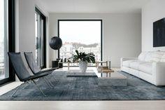 Wohzimmer mit weißer Couch, grauem Teppich, schwarzen Lederstühlen, Designer-Couchtisch, Pflanzendeko