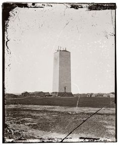 """Washington Monument as it stood for 25 years, 1860. George did NOT want any monument erected for him; he chose to be buried on his home estate. He considered monuments to be objects of conceit and arrogance. In 1833, the 100th anniversary of Washington's birth, a group of concerned citizens formed the Washington National Monument Society. This started a process in 1888. (A 25-year gap in this picture and the """"color band"""" we see to this day.) Photograph by Mathew Brady."""