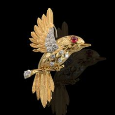 Fine brooch designed as an 18ct yellow gold bird perched on a branch with a cabochon ruby eye and diamond set body to a spray of tail-feathers by Cartier, London c1960's. Hancocks & Co (Jewellers) Ltd. www.hancocks-london.com