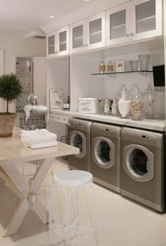 Laundry Room- Love the apothecary jars holding detergent, but what the heck is that third machine for?