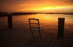 Lonesome chair on deck at sunset over the Gulf of Mexico.  Photo taken by ELLIS of Mississippi GulfCoast for the Dandelion paper.