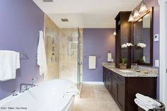 A contemporary bathroom with gold granite countertops, neutral tile floors and bold, purple paint. Click to see a $495 small bath makeover that'll inspire you to try something new.