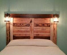 Headboard my Husband and I made from pallet wood! The top board was from a 100+ year old barn. Lightning from Lowes. Total cost was about $50 that includes lighting, minimal staining, and clear coat varnish.