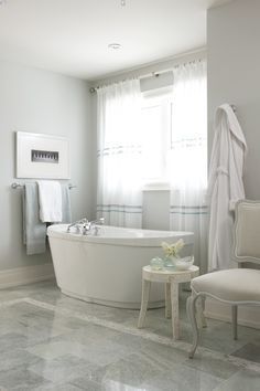 Glam bathroom with freestanding tub placed in front of window covered in white curtains over marble tiled floor accented with mosaic inset tiles.
