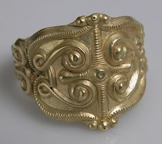 Ring, 4th-5th century, Celtic, gold. These rings evoke the splendor of the Celts and their love of personal adornment. The upper ring is one of the most lavish surviving examples. The rams' heads are similar to those on the great gold neck ring from Frasnes-lez Buissenal also exhibited in this case. The two smaller rings present a combination of tendril motifs, some echoing symmetrical designs that appear to be abstractions of a face.