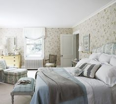 Laura Wilmerding Interiors Lighthearted Clianthus wallpaper by Nina Campbell creates a perpetual summer in the master bedroom. Wilmerding tossed in a handful of other patterns for a casual feeling. The headboard and chair with matching ottoman are upholstered in Colefax and Fowler's Lincoln floral