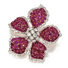 18 KARAT GOLD, PLATINUM, RUBY AND DIAMOND BROOCH, DAVID WEBB Designed as a flowerhead set with round and single-cut diamonds weighing approximately 9.75 carats, and round and oval rubies weighing approximately 25.00 carats, signed David Webb and Webb, one diamond missing.