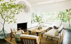 Naturalistic- The use of the naturalistic elements in this mid-century modern living room creates a light, airy feeling. The textures of the raw edge coffee table, the trees in the corners, and the natural sisal carpet create a naturalistic effect.