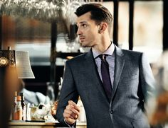A dapper grey suit looks good on anyone, add a dash of colour with a deep purple tie