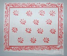 A rectangular white cotton cloth with four borders of floral motifs enclosing a repeating pattern of red floral motifs painted freehand and with the use of a stencil. The cloth was specially commissioned as part of a sequence illustrating the historical development of kanga design.