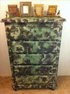 DIY Camoflauge dresser... Super simple find a few branches from trees pick out camoflauge colored spray paint (walmart) then go to town hold the branches against the dresser and spray around the leaves and branches.  Now I just have to find some knobs for the dresser (deer antlers? from any hunting site or store) and maybe even add some deer or duck decals to the drawers (stines or online) :)