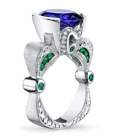 Engraved platinum ring featuring a 5.56ct oval tanzanite accented with 0.54ctw of tsavorite garnets, and 0.21ctw of white diamonds. This piece is available for reproduction. Contact us to find out mor