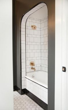 Black and white bathroom features an arched alcove filled with white subway tiles mixed with white square tiles finished with black grout lined with a rose gold shower kit over a drop in tub.