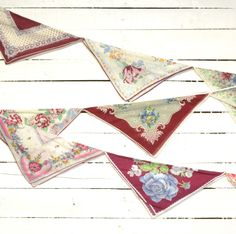 Add a sweet and romantic touch to your special celebration with this hand-crafted bunting. Made of eight, uncut, vintage hankies makes it finished on both sides, allowing it to be hung freely. They are sewn onto a white, twisted rope holding them all together and finishing the top edge. Simple loops accented with wooden beads make it easy to hang. The overall length of the bunting is approximately 13 feet. Approximately 12 inches from the last hankie to the end of the loops for hanging.