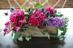 Magenta dahlias, blue thistles, and greenery in a planter box | Photo by Roots of Life | Floral design by Fleur du Jour