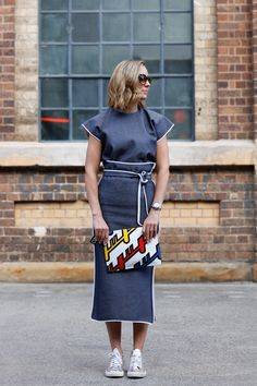 A structured midi dress with white piping sis worn with metallic sneakers and red yellow and blue graphic clutch.