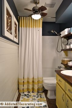 The shower curtain with the pleated ruffles was made from a queen size bed sheet, and accented with yellow striped fabric that was provided by Fabric Warehouse Direct.   Read more: http://www.addicted2decorating.com/small-bathroom-makeover.html#ixzz2PzRuGC1k