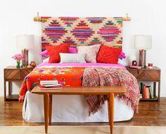 Cabeceira interessante feita com um varão de madeira e um tapete de tear. Cores bonitas e bem escolhidas
