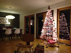 A great picture from a happy customer in Seattle! This effect was created with 60 yards of red nylon cord, 150 feet of diamond lights on wire from Restoration Hardware, lots of red balls, and other assorted ornaments. Thanks for sharing, Jonathan!  | The Jubiltree Company, LLC  | Modern Wood Christmas Trees