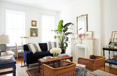 """The starting point for the design was the navy settee. """"I love the classic features of it—the wooden legs and, of course, the color—but the clean lines and the very rectangular angles just felt so fresh,"""" Amy says. The walls were painted Benjamin Moore's Chantilly Lace."""