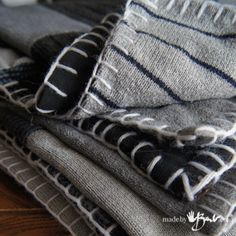 """Upcycled sweater blanket - I like the blanket stitch done in yarn around the perimeter of the blanket.  She used 9"""" squares and tied the blanket with yarn at the points where the squares were pieced together."""