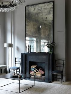 5 Solutions for a Non-Working Fireplace: Piled up vintage books in a stunning moody room by Erin Swift   Scotch and Nonsense