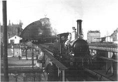 Een locomotief rijdt over de brug aan de oostkant van het Centraal Station van Amsterdam. 1890