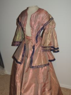 "c. 1860 iridescent dress; ebay seller shastasvintage; peach/greenish gold silk taffeta; jacket hooks down front, boned in seams, lined in cotton; sleeves puffy at top, gathered mi arm, trimmed with iridescent silk ribbon in navy & peach; wide flared peplum; skirt smooth around waist, center back some gathering & tucks, waistband faced with red, white & blue plaid linen; skirt lined in loosely woven gauze fabric; bust: 33""; waist: 22""; skirt waist: 23""; length: 42""; hem width: 136""; 3.15…"