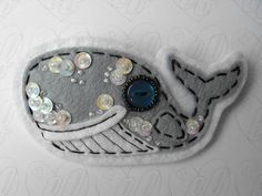 felt whale.  Make with paper, but weave yarn around the edges and glue on buttons or instead of yarn use black glue.