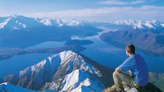 A hiker enjoys the view along the Roys Peak Track, Mount Aspiring National Park