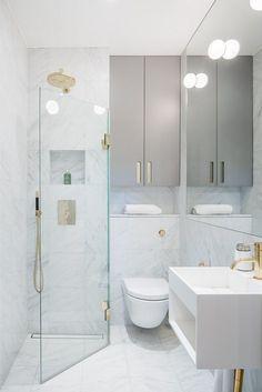 Mała, funkcjonalna łazienka w jasnych barwach – podwieszane szafki i duże tafle szkła w kabinie prysznicowej optycznie powiększają przestrzeń.