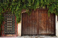 Wooden doors and a colorful metal grill door at an entrance to walled casa in Ajijic, Mexico. Filename: fancyandplain.jpg Copyright Susan Isakson