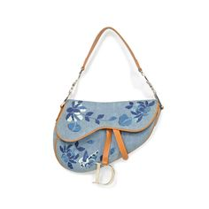 Reminiscent of John Galliano's tenure at Christian Dior, and true to his design aesthetic. The Saddle style was all the rage during his reign at the house of Dior. This Dior Saddle bag from Spring/Summer 2005 is crafted in a denim with camel toned leather trim and details. Embroidered with a floral and butterfly design, it also features silver toned metal hardware. The bag also features a velcro closure. The interior is lined with fabric and has a zippered pocket.   Bag measures: Length…