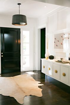 Contemporary entry features full wall wainscoting framing floating white lacquer cabinet accented with brass hardware and topped with Faux Python Tray as well as black drum pendant, Arteriors Anderson Iron Pendant, over white and brown cowhide rug alongside black front door.