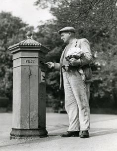 Man posting a letter holding a cauliflower, 1949.