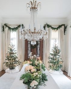 Welcome to a House Party That's Brimming With Christmas Spirit | Two trees flank either side of this grand dining space, both sparkling with old-fashioned tinsel from Germany and chandelier crystals. At the center of the table, an abundance of earthy greens—potted maidenhair ferns, white roses, cedar, cryptomeria, eucalyptus, white narcissus, and white hydrangeas—are displayed in sterling silver vessels.  #homedecor #marthastewart #christmas
