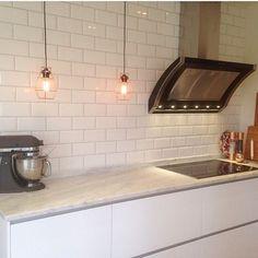 Hemma hos @anette_raa pryder en svart Rustik den vita kakelväggen. Den svarta lacken bryter av från det förövrigt ljusa köket. #fjäråskupan #rustik #svartlackat #rostfritt #spiskupa #köksfläkt #kakel #tile #belysning #carraramarmor #marble #stilrentkök #moderntkök #scandinaviandesign #kitchenaid