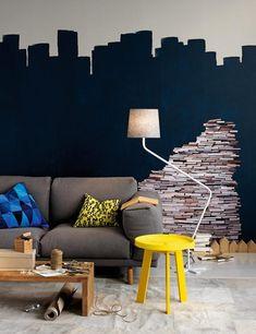 Tøffe møbler og stilig, malt veggdekor i denne stuen. Boksticker på veggen fra Bolia. Rest sofa fra Muuto, gul pute med bokstaver fra Bolia, blå, grafisk pute fra Ikea, grovt trebord fra Verket Interiør, canvas gulvteppe fra Palma, Groggy lampe fra Northern Lighting og Peace gult sofabord fra Bolia.