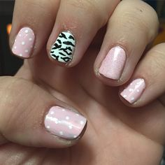 White dotted pink nails and zebra midfinger. Ring finger with glitter.