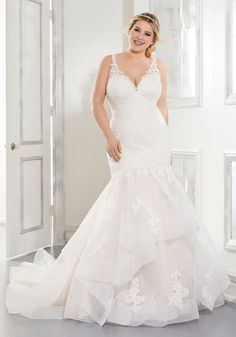 This mermaid wedding dress in tulle and lace has a sleeveless bodice and a v-neck neckline.