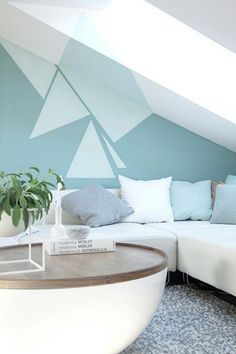 peinture décorative dessin géométrique triangulaire en deux nuances de bleu dans le salon avec un canapé d'angle blanc et table basse ronde