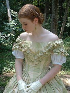 Very understated silk dress with evening bodice. Her bodice has the sharp pointed waist and off the shoulder neckline common in ball and evening gowns.