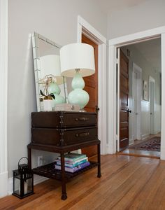Foyer table from old suitcases and wood stand, large mirror and lamp.