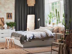 Wit bed met lades in een grote slaapkamer met bakstenen muur, grijze gordijnen en jute vloerkleden.