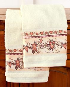 """Bring a little country charm into your bathroom with this set of 2 Hearts and stars hand towels. Each piece features a rustic patchwork pattern with images of hearts, stars, berries and vines. Set of 2 Hand Towels, 15"""" x 25"""", each. 